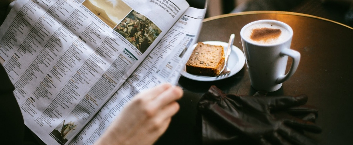 Picture of a newspaper being held by a coffeetable